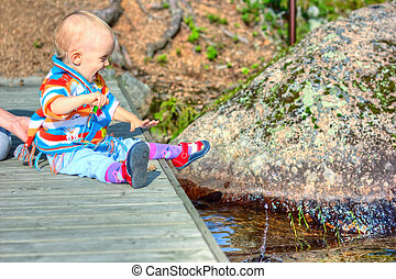 Little kid sitting on bridge