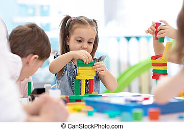 Little kids build block toys at home or daycare. Emotional kids playing with color blocks. Educational toys for preschool and kindergarten children.