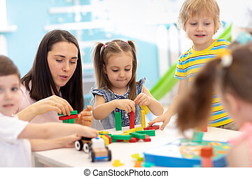 Little kids build block toys at playschool or daycare. Kids playing with color blocks. Educational toys for preschool and kindergarten children.