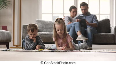 Little kids drawing pictures while parents using digital tablet.