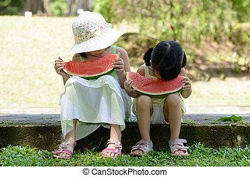 Little kids eating watermelon