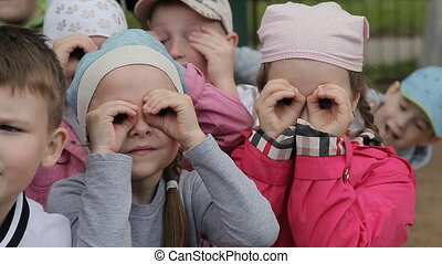 Little kids girls and boys looking through imaginary binoculars, guys pretending to look through binoculars on the playground
