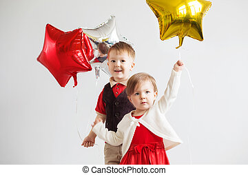 Happy children with colorful shiny foil balloons against a white background