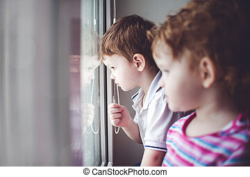 Little kids looking out the window.