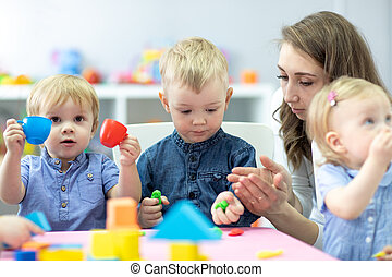 Little kids molded from clay toys. Teacher play with children.