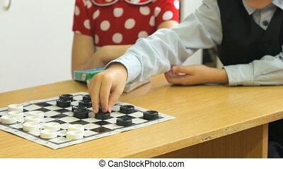 Little kids play checkers at kindergarten.Close-up - Little...