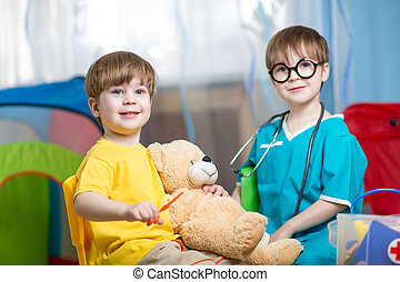 little kids play doctor with plush toy