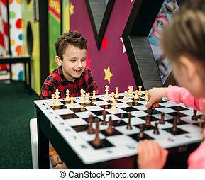Little kids playing chess in entertainment center