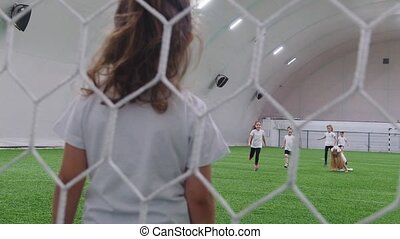 Little kids playing football in indoor football arena. Mid...