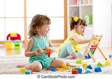 Little kids playing with abacus and constructor toys in kindergarten, playschool or daycare center