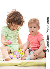 Little kids playing with Easter eggs