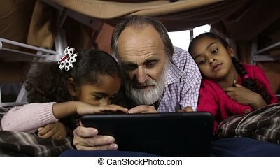 Little kids teaching grandfather to use tablet