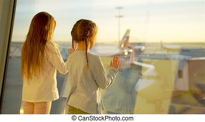 Little kids together in airport waiting for boarding near big window