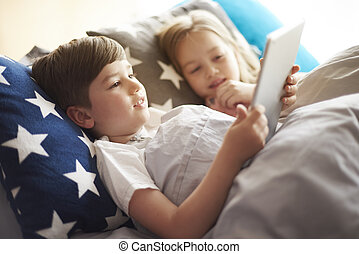 Little kids with digital tablet in bed