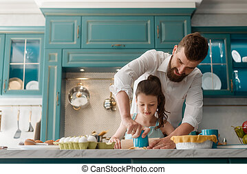Little lady making cookies with daddy in kitchen