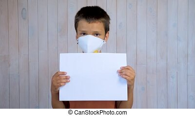 Little latin boy in a medical mask looking at the camera holding a sheet of a4 paper. Mockup in the hands of a child. Stay at home concept. Respiratory protection. hildren and Covid-19, Coronavirus