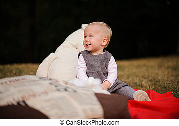 Little laughing baby girl sitting on a blanket in the park