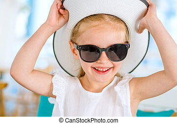 Little laughing blond girl in black sunglasses