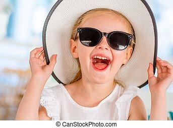 Little laughing blond girl in black sunglasses