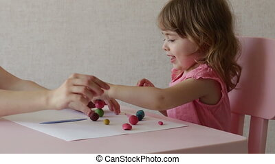 Little laughing girl and mom play with plasticine at home