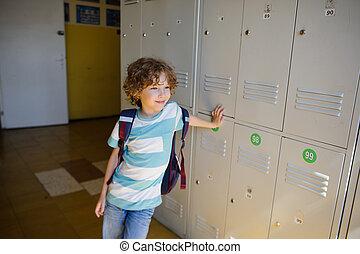 Little learner standing near lockers in school hallway