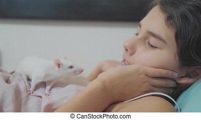 little lifestyle girl is played on a bed with a white homemade handmade rat mouse. funny video rat crawling over a little girl. girl and white mouse pet concept