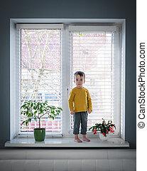 Little loneliness kid boy stay on windowsill