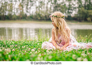little lonely girl sitting in the grass by the river