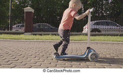 little lovely boy on the kick scooter in the park. Slow motion