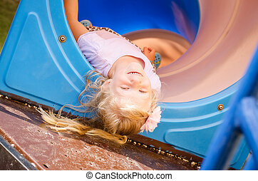 little lovely girl playing in playground up side down