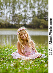 little lovely girl sitting in the grass by the river
