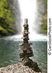 little man made of stones to indicate the right direction in the mountains is a small pond with waterfall