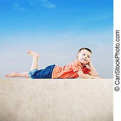 Little man relaxing after tiring play - Little boy relaxing...