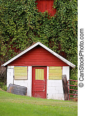 Little Milk House Structure with Old Door Attached to Large Red Dairy Barn Covered in Green Vines