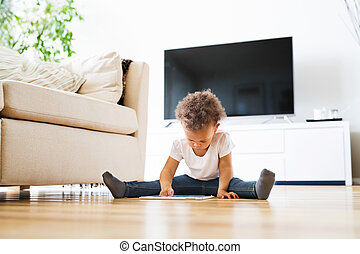 Little mixed-race girl at home playing game on tablet. -...