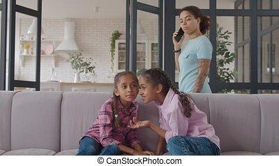 Little mixed race girls sharing secrets on sofa - Cheerful ...