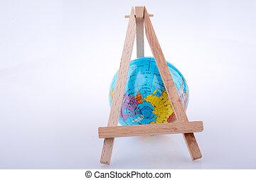 Little model globe put under a tripod on white background