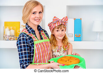 Loving family concept. Happy mother cooks with her daughter.