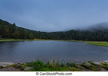 little mountain lake with dense rain clouds in the nature while hiking
