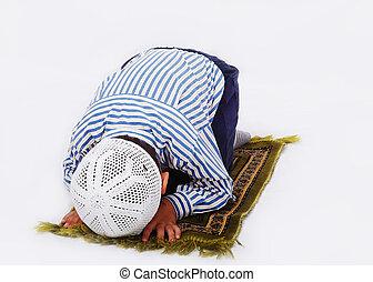 Little muslim boy is praying on traditional way