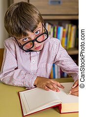 little nerdy boy with geeky goggles, writting in a book