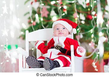 Little newborn baby boy in Santa outfit sitting uder a Christmas