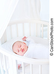 Little newborn baby boy sleeping in a white round crib with cano