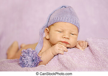 Little newborn baby in a funny hat sleeping in white blanket, lying on bed.