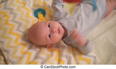 little newborn baby lies on his back in the crib