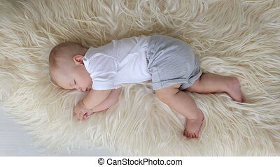 Little newborn boy sleeping on a fluffy blanket at home in the bedroom.