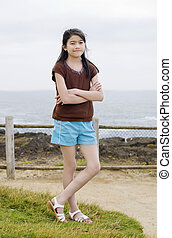 Little nine year old girl posing arms crossed by ocean