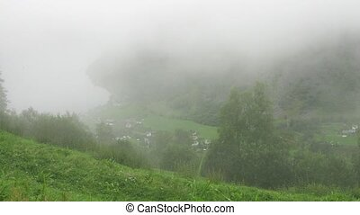 Little Norwegian village covered in fog, zoom view, time...