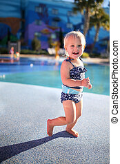 Little One Year Old Girl Playing Outside at The Splash Pool on Vacation