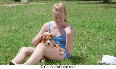 Little owner with american staffordshire terrier puppy dog on grass